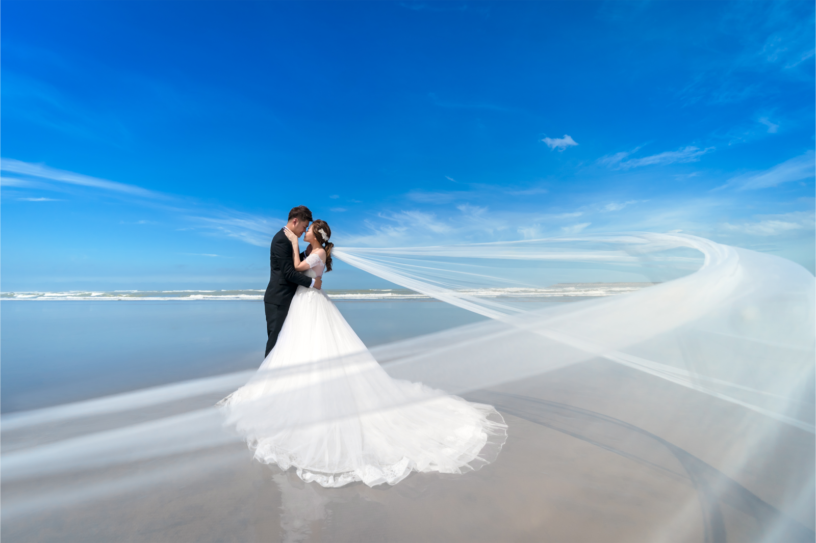 wedding couple standing by ocean with wedding veil in wind alpha 9