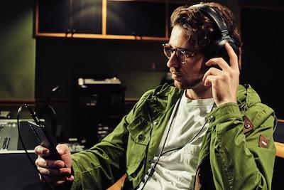 Mężczyzna w studio słuchający muzyki na Xperii 1 III ze słuchawkami