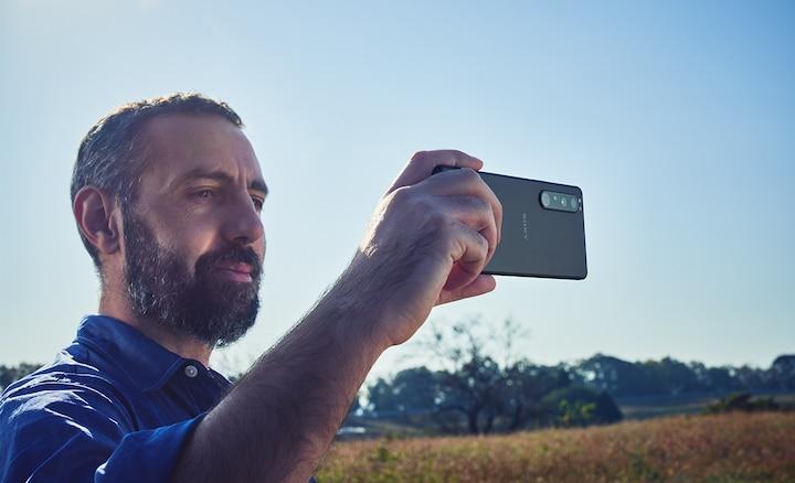 Mężczyzna używający Xperii 1 III do filmowania w plenerze