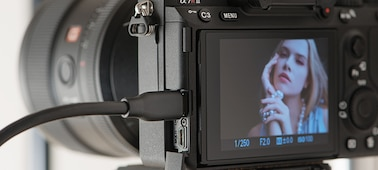 Image illustrating fast data transfer, showing side/rear view of camera with USB cable attached