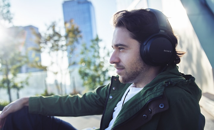 Man listening to music with wired headphones on