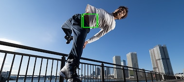 A man outside on a bridge jumping with a green autofocus square in the middle of his  body