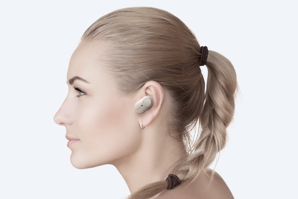 Studio shot of woman wearing WF-1000XM3 headphones with customisable touch controls.