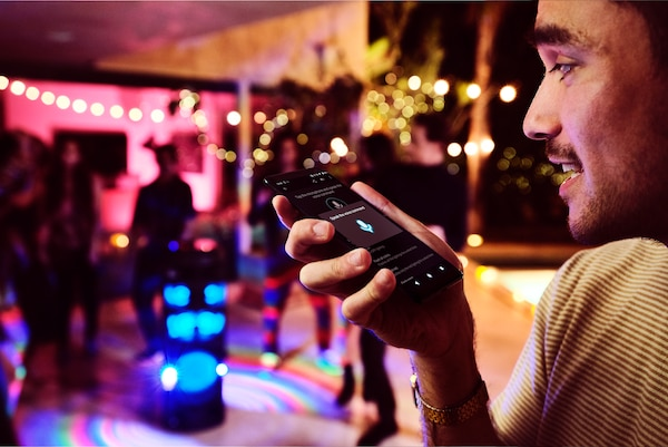 Partygoer using Voice Control via Fiestable app on their smartphone