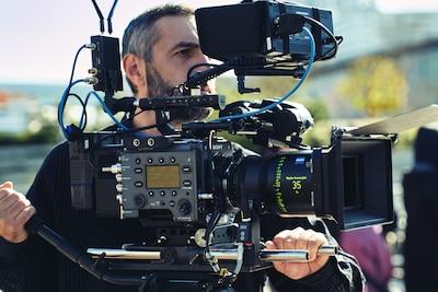 Mężczyzna filmujący na zewnątrz kamerą filmową