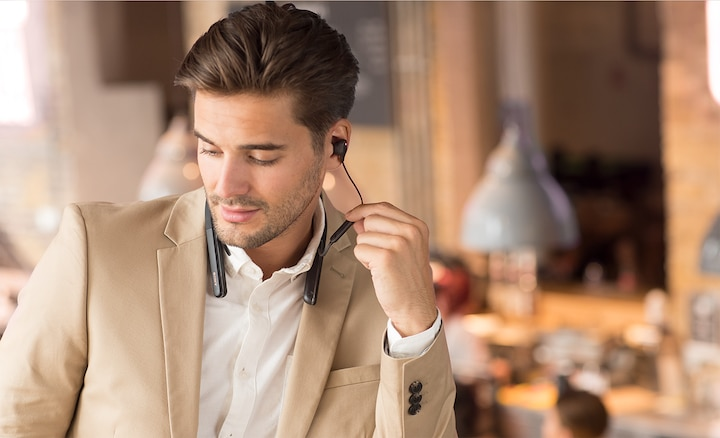 Lifestyle image of man using inline controls on WI-1000XM2 headphones.