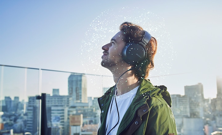 Man listening to music on headphones in a city with an illustration of 360 sound around his head