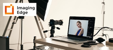 Image of studio illustrating Imaging Edge PC application, with camera on tripod, and PC with camera image on screen