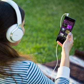 Woman wearing Sony headphones connected to Walkman