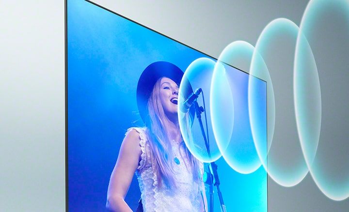 Tv showing a woman singing with sound waves coming from the microphone on screen