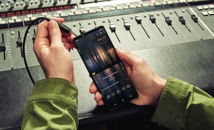 3.5mm cable being plugged into Xperia 1 III in front of a mixing desk