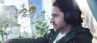 Man listening to music on wired headphones