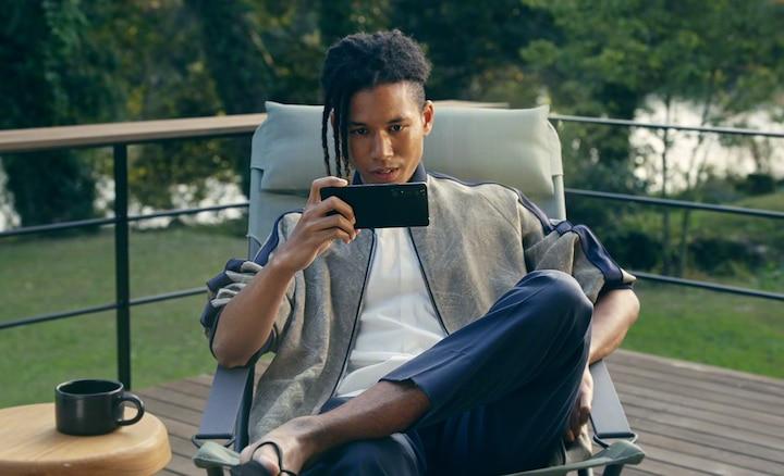 Mężczyzna siedzący na zewnątrz patrzący na Xperię 1 III