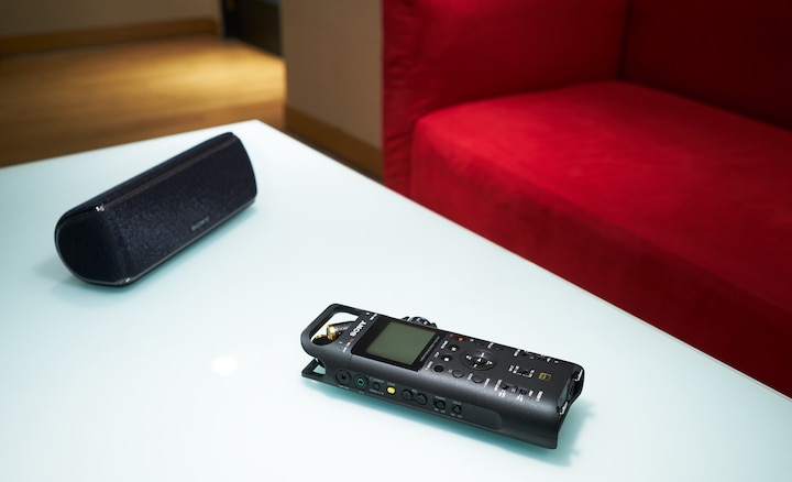 Sony PCM-D10 and BLUETOOTH® speaker on a table in front of a sofa