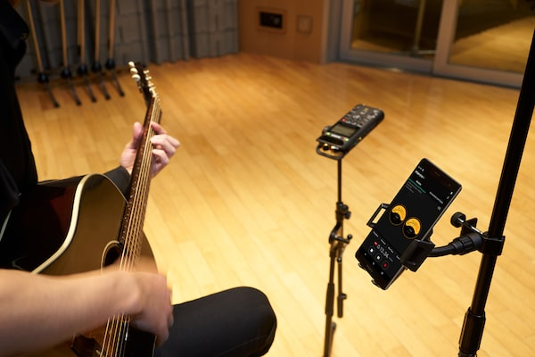 Guitarist plays with the audio recorder fixed to studio stand and a smartphone displaying the REC level in analog view